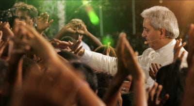 Pastor Benny Hinn laying hands on people
